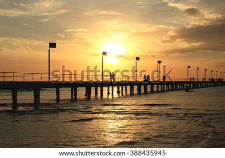Pier,sunset and silhouettes, Frankston, Victoria, Australia - stock photo
