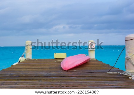 Pier with boat on a tropical beach - stock photo
