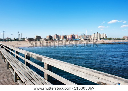 Pier with Coney Island beach in the background, New York City. - stock photo
