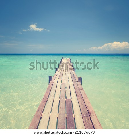 Pier wooden bridge towards sea, tropical island sea view in vintage style. - stock photo