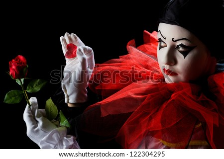 Pierrot looking sad and taking petals off a red rose - stock photo