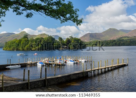 Piers and boats on edge of Derwentwater in English Lake District in early morning