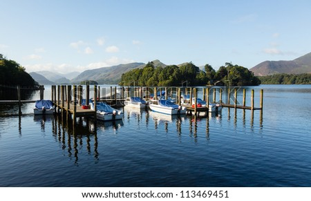 Piers and boats on edge of Derwentwater in English Lake District in early morning - stock photo