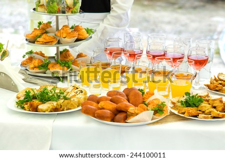 Pies, eclairs and drinks on a banquet table - stock photo