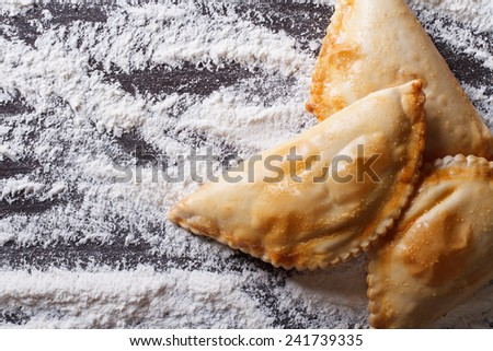 pies empanadas closeup on a floured table. horizontal view from above  - stock photo