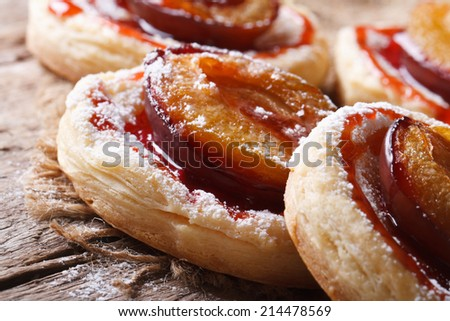 Pies of puff pastry with plums macro on an old table. horizontal   - stock photo