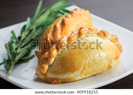pies with meat on a plate with a sprig of greenery - stock photo