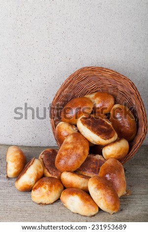 pies with meat or cabbage fallen out of a wicker basket on a wooden background - stock photo