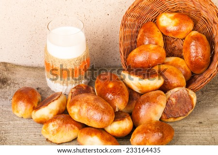 pies with meat or cabbage in a wicker basket and a glass of milk on a wooden background.  - stock photo