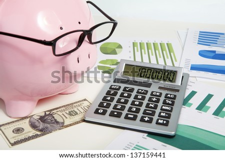 Pig bank and a lot of diagrams and calculator - stock photo