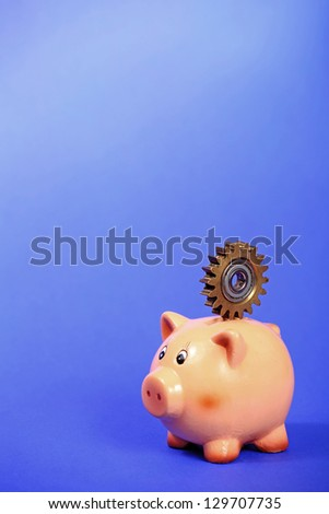 Pig bank holding old metal gear on the back over purple background - stock photo