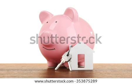 Pig money box and paper decor on a table isolated on white - stock photo