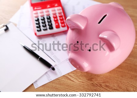Pig moneybox and calculating equipment on desk closeup - stock photo