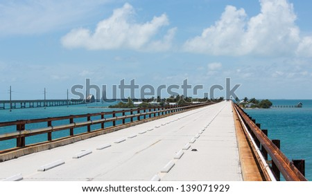 Pigeon Key with the old Seven Mile Bridge going through it. The new bridge bypasses it. The handrails seen on the old bridge are the original railroad tracks used on the Overseas Railroad. - stock photo