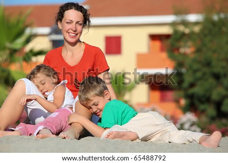 Pigeon pair play with  mother on  beach on sand, lying for it on knees, focus on boy - stock photo