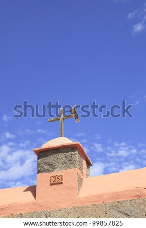 Pigeon sitting on a wooden cross of a church - stock photo