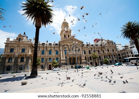 pigeons flying over city hall of cape town, south africa - stock photo