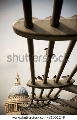 Pigeons on the Millennium Bridge in London, with St Paul's Cathedral in the background - stock photo