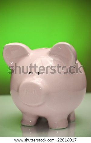 Piggy bank against green backdrop. Savings and economy concept. - stock photo
