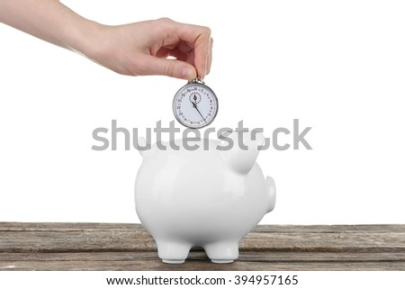 Piggy bank and a hand holding timer above it on white background - stock photo