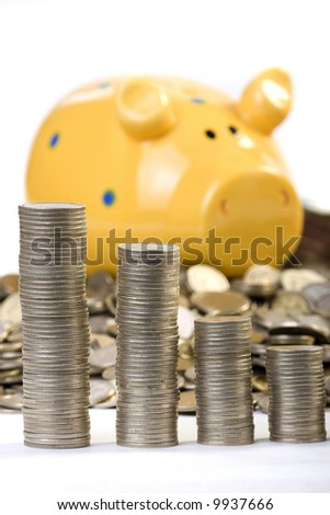Piggy bank and a lot of coins behind of coins chart - stock photo