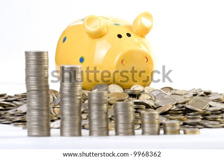 Piggy bank and a lot of coins behind of coins chart. Focus on Piggy - stock photo