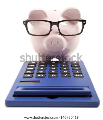 Piggy bank and calculator isolated on white background - stock photo