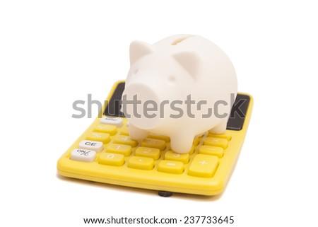 Piggy bank and callculator isolated on white background  - stock photo