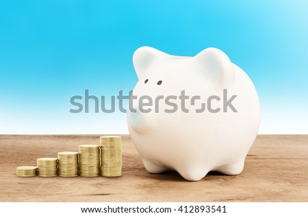 Piggy bank  and gold coin on wood floor with blue background ,save success business financial concept