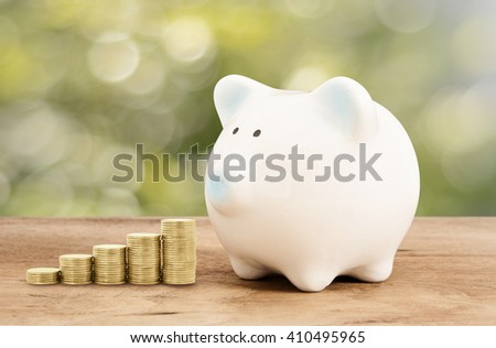 Piggy bank and gold coin on wood floor with green bokeh background , ,save success business money concept art abstract background
