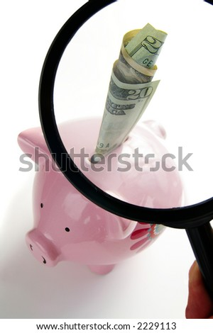 Piggy bank and hand with magnifying glass - stock photo