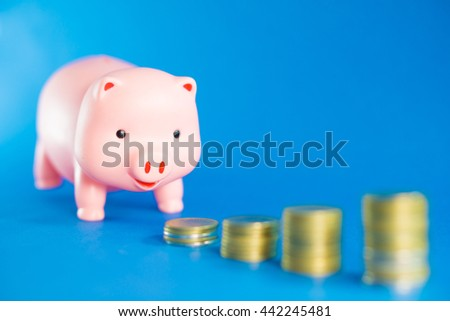 Piggy bank and money tower on blue background.Saving money Concept.Selective focus. - stock photo