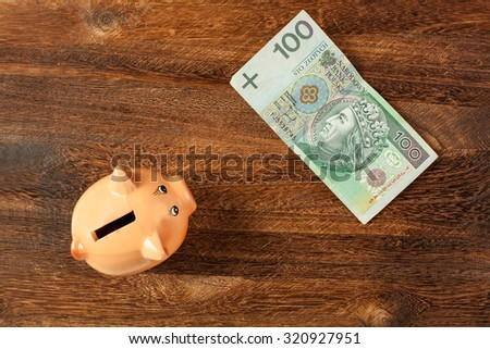 Piggy bank and one hundred polish zloty note on brown wooden background. View from top. - stock photo
