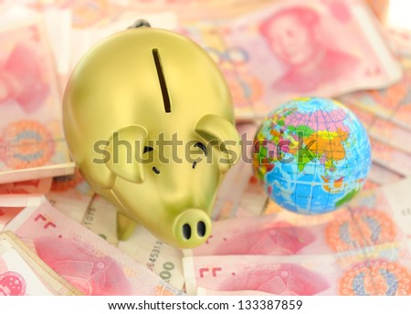 piggy bank and one-hundred rmb bill with earth - stock photo