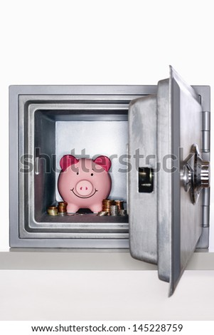 Piggy bank and piles of coins in open safe - stock photo