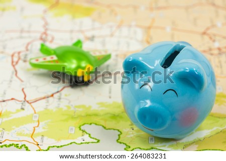 piggy bank and plastic airplane toy  over map ,abstract background to saving money for travel concept - stock photo