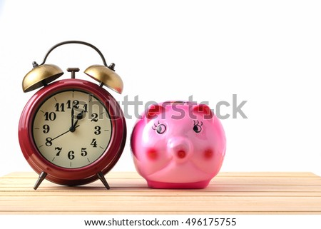 Piggy bank and retro clock on a wooden floor with a white background,The concept of time to save money.