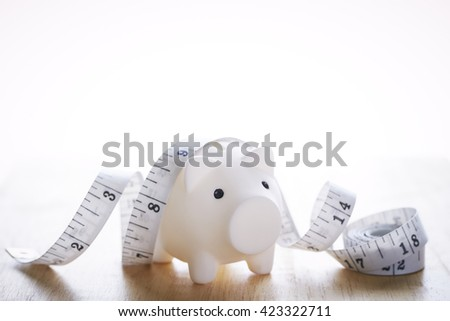 Piggy bank and tape measure - stock photo