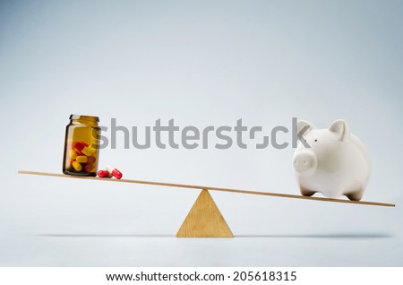 Piggy bank balancing on seesaw over a bottle of pills - stock photo