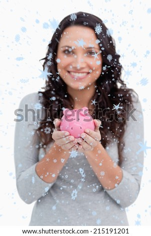 Piggy bank being held by smiling woman against snow falling - stock photo