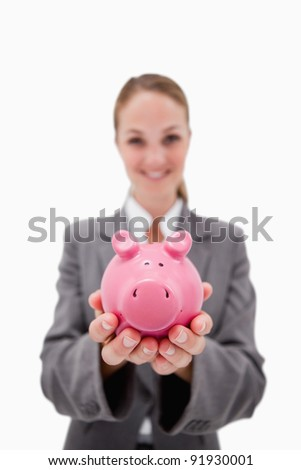 Piggy bank being offered by smiling bank employee against a white background - stock photo