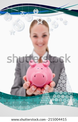 Piggy bank being offered by smiling bank employee against christmas frame - stock photo