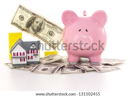 Piggy bank beside graph and miniature house on white background