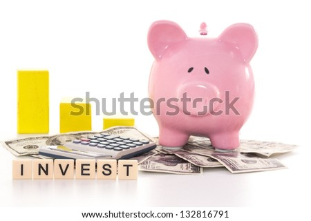 Piggy bank beside graph calculator and invest spelled out in plastic letter pieces on white background