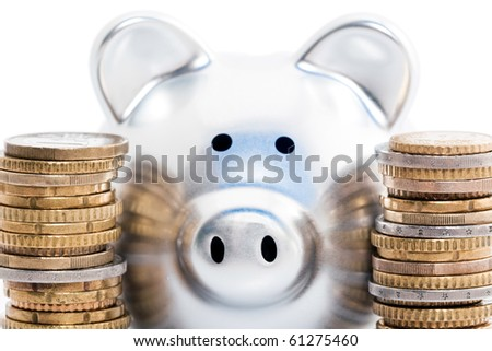 Piggy bank between stacks of golden and silver coins, isolated on white background