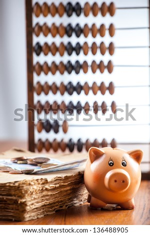 Piggy bank by old book with banknote and coins, abacus seen on background - stock photo