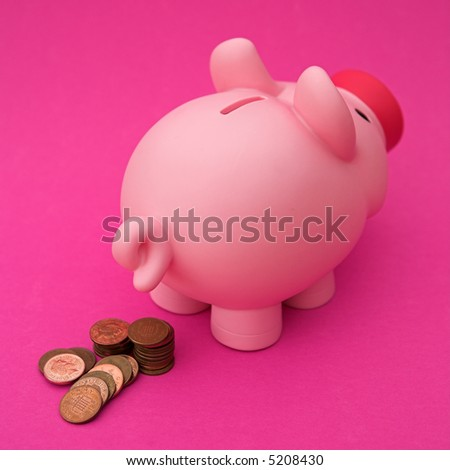 Piggy bank 'depositing' some pennies - shallow dof - stock photo
