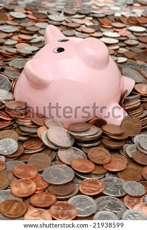 Piggy bank drowning in a sea of coins - stock photo