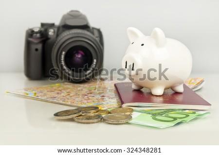 Piggy bank, euro money, passport, camera and map. Saving on travel. - stock photo