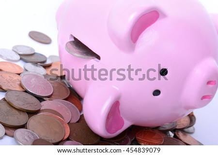 Piggy bank fallen over with coins pouring out concept of debt or finance issues